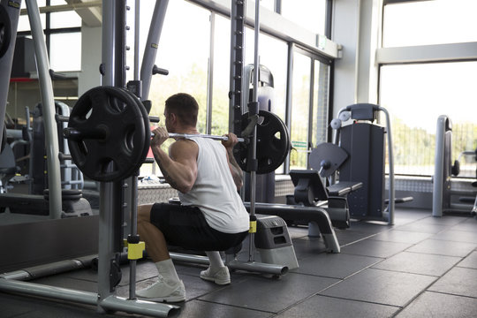 Rear View Of Young Man Lifting Weights In Gym
