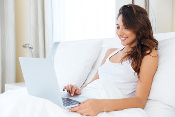 Smiling woman relaxes in bed with a laptop computer
