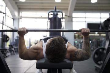 Man Bench Pressing Weights In Gym