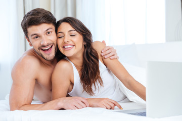 Beautiful young couple using laptop and looking at camera