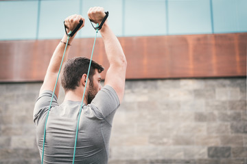 urban fitness man looking aside while working out  triceps using expander. Sporty strong male exercising outdoors with elastic straps. Wall mural
