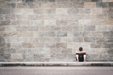 exhausted fitness man outdoor sitting on the floor leaning on wall. Sport breakdown concept with copyspace.