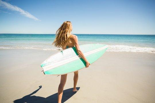 Woman walking with surfboard on beach