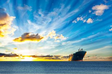 Cargo ship sailing on sea at sunset.