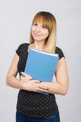 Girl with a dreamy look standing with folders in hands