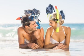 Young couple wearing diving mask lying on beach Wall mural