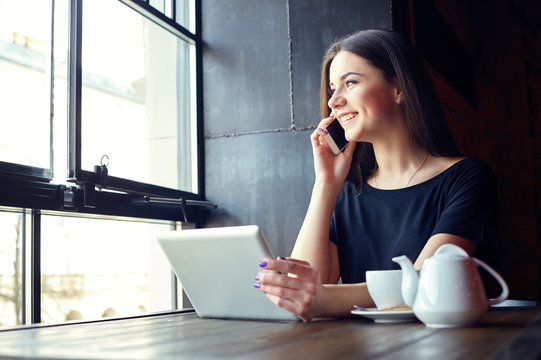 Young attractive girl talking on mobile phone and smilling while sitting alone in coffee shop during free time and working on tablet computer. Happy female having rest in cafe. Lifestyle, coffee