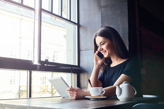 Young attractive girl with cute smile talking on mobile phone while sitting alone in coffee shop during free time and working on tablet computer. Happy female having rest in cafe. Lifestyle, coffee