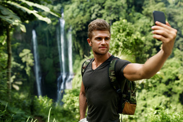 Take Photos. Tourist Man Making Selfie Photo With Mobile Phone On Summer Vacation. Beautiful Handsome Happy Cheerful Young Male Traveler Enjoying Nature Of Tropical Forest. Travel, Tourism, Technology
