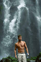 Water Drink. Healthy Man With Sexy Fit Body Holding Bottle Of Fresh Pure Water, Enjoying Nature Near Beautiful Tropical Paradise Waterfall On Summer Travel Vacation. Health Care, Hydration Concept
