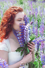 Redhead woman with long hair in lupine field