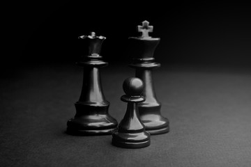 Chess. Black Pawn, King and Queen on black background.