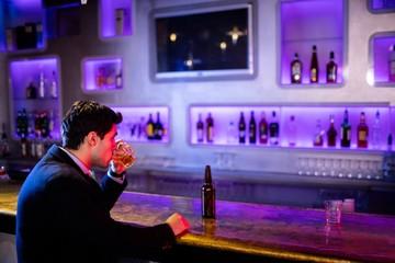 Man drinking alcohol at bar counter