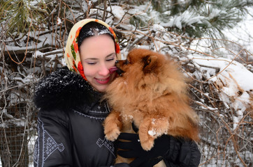 Beautiful Russian girl with a dog in winter