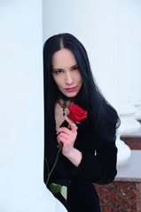 beautiful young brunette woman with a red rose in hands