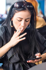 Young girl sitting in cafe, smoking cigarette and typing on smart phone