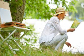 Seniorin malt ein Bild in der Natur im Sommer