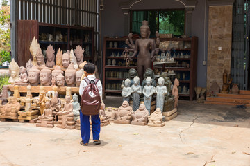 boy looks at statue of a Buddha