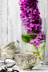 Fototapete - Still life with tea and branch of lilac