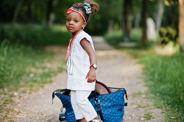 Funny african baby girl with big bag at park