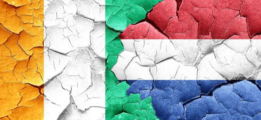 Ivory coast flag with Netherlands flag on a grunge cracked wall