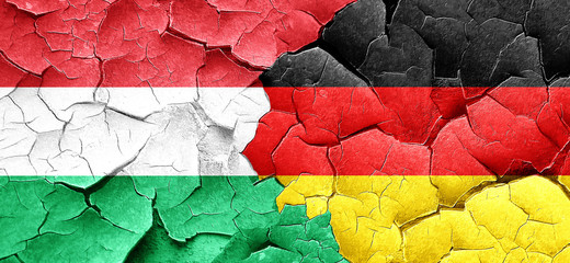 Hungary flag with Germany flag on a grunge cracked wall