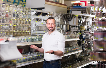 man standing next to showcase with various plastic rawlplugs an