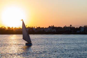 Tourist sailboat at Luxor waterfront during sunset.