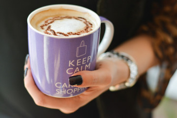 One big cup of cappuccino, white milk coffee held in hand: keep calm and carry on shopping concept