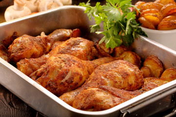 Roasted chicken legs with potato chips and vegetables