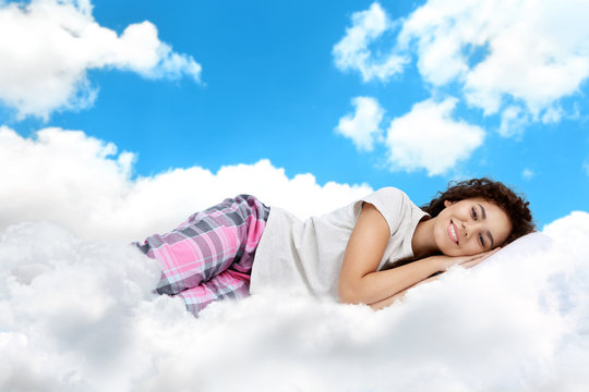 Beautiful girl lying on blue cloudy sky