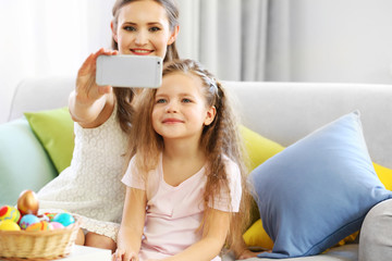 Mother and daughter making selfie, indoors