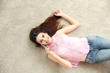 Beautiful girl with cellphone lying on floor