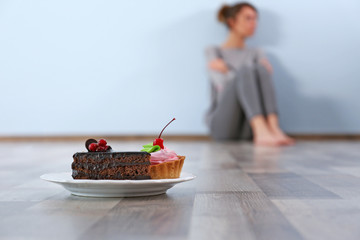 Desperate woman sitting on the floor on grey wall background. Eating disorder concept