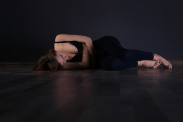 Anorexic girl lying on the floor on dark wall background