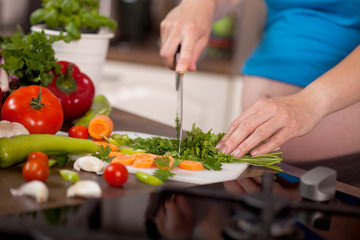 Pregnant woman preparing a healthy meal in the kitchen