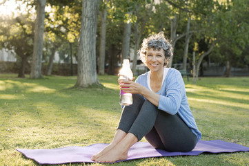 Portrait of mature woman sitting on exercise mat and drinking water at field
