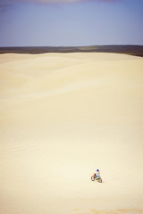 Teenage girl riding bicycle on desert