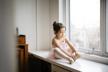 Girl wearing ballet shoes on table