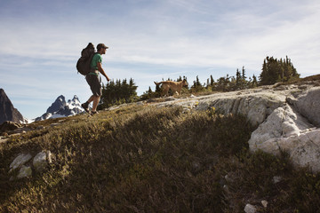 Side view of man hiking with dog on mountain against sky