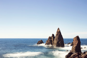 Scenic view of rock surrounded by ocean against clear sky