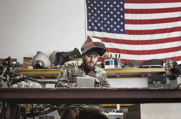 Serious manual worker working on machinery against American flag at auto repair shop