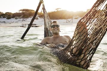 Young man lying on hammock in lake