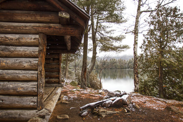 Old log cabin by lake and trees in forest