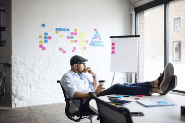Thoughtful businessman holding disposable cup while sitting at creative office