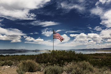 American flag waving against a cloudy sky