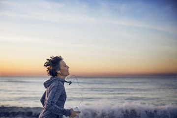 Woman jogging at beach against sky