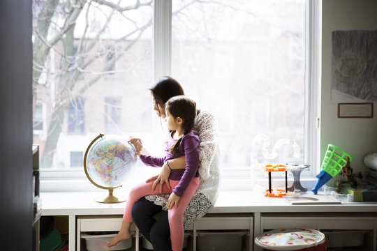 Mother and daughter looking at globe at home