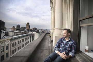 Man sitting on balcony against cityscape