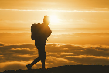 Silhouette female hiker walking on mountain during sunset